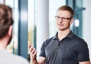 Coach Marc Kaltenhäuser im Dialog mit Klient stehend